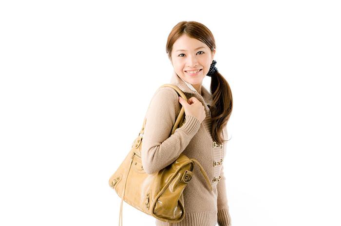 ブランドバッグを持って嬉しそうな女性